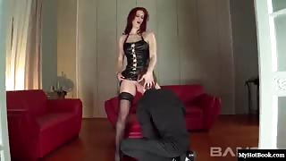 Sexy redhead, Mira Sunset, wearing some provocative lingerie, thigh-high stockings and high heels,